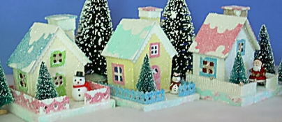 If you are paying attention, you'll notice that the snowman from the photo of the finished project house above has traded places with the santa from the house from our title photo (center), and a new plastic snowman is now guarding our project house.  In the meantime, Santa has moved to a house we haven't seen yet in this article. I hope this just means that Howard doesn't have his accessories glued down yet, and that they're not playing 'musical houses' on their own. What this photo is supposed to show is that Howard doesn't exactly build these one at a time.   Click for bigger photo.