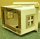 This sub-base made of corrugated cardboard provides a little more strength to the house and gives a better surface for gluing to the base.  Click for bigger photo.